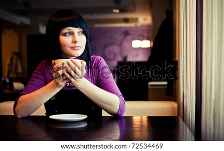 girl hold cup of coffee in hand look in window
