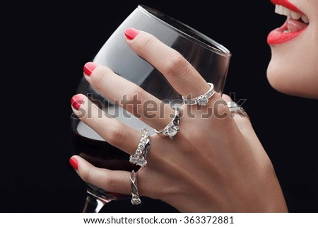Girl hold glass of wine in the hands all in rings close -up, red lipstick. Woman smile lavishly expensive #363372881