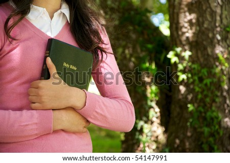 Girl holding a Bible in nature