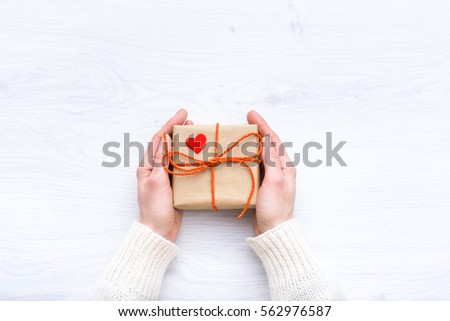 Girl holding a gift in their hands. Box with surprise on the wooden background. A gift for the holidays. Love story. Surprise. Present for Valentine\'s Day