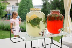 Girl holding a glass of colorful natural fruits lemonade during backyard barbeque party at summer, elegant decoration, luxury catering, drink and buffet standing reception, festive celebration