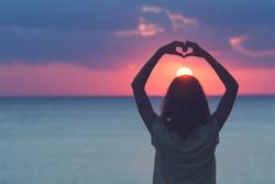 Girl holding a heart shape for the ocean / sea sunset.