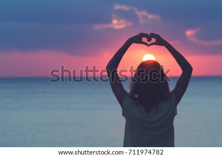 Girl holding a heart shape for the ocean / sea sunset.