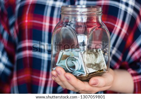 girl holding a jar for donations, fundraising, charity with copy space #1307059801