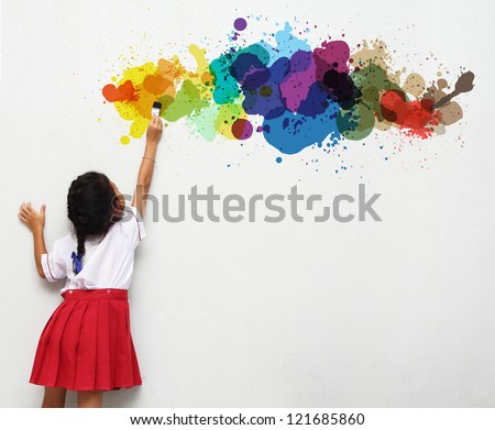 girl holding a paint brush painting on a white wall
