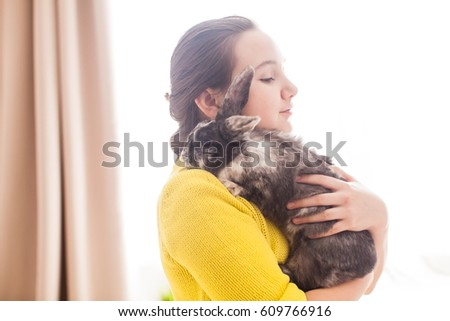 Girl holding a real Lop-eared rabbit and posing with it on camera #609766916