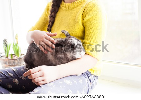 Girl holding a real Lop-eared rabbit and sitting on the windowsill #609766880