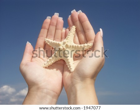 Girl holding a starfish in two palms against blue sky