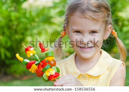 girl holding a sticks with vegetables (cucumber, pepper, tomato). Concept of healthy food. - stock photo