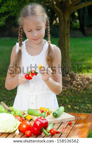 girl holding a sticks with vegetables (cucumber, pepper, tomato). Concept of healthy food.