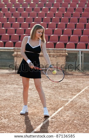 Girl holding a tennis racquet while standing on a tennis court for lessons.