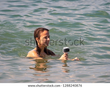 Girl holding action camera in waterproof case. Compact gadget waterproof, support 4k video, voice controls and is often used in extreme photography