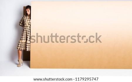 Girl holding big cardboard blank surface area banner , fashion concept
