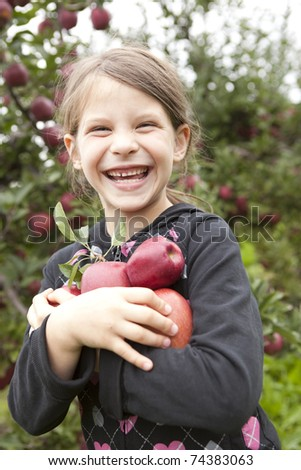 girl holding bunch of apples and laughing