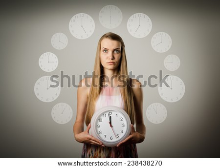 Girl holding clock in her hands. Time concept. Several minutes to twelve.