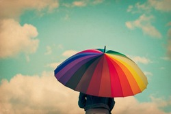 Girl holding colorful rainbow umbrella up to the sky, grunge vintage filter.