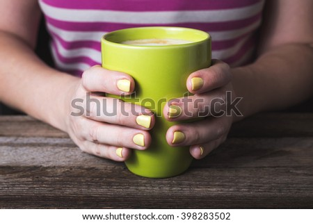 Girl holding cup and have a yellow manicure #398283502