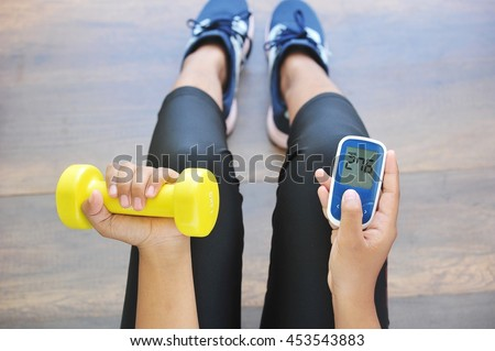 Girl holding dumbbell and glucose meter,concept for diabetes lifestyle and healthy.