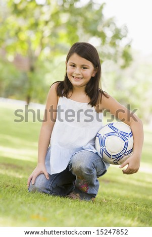 Girl holding football in park looking to camera