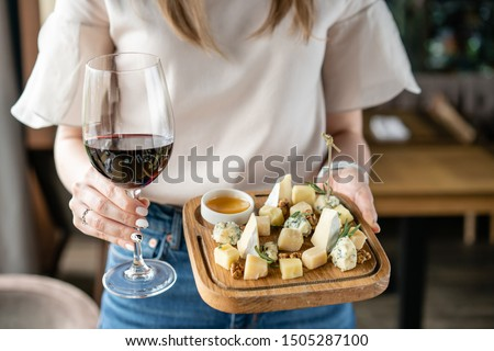 Girl holding glass red wine and wooden plate with cheese. Delicious cheese mix with walnuts, honey. Tasting dish on a wooden plate. Food for wine.