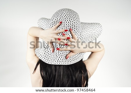 Girl holding his hat on a background