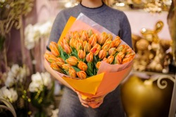 Girl holding in her hands a wonderful bouquet of orange tulips decorating with a green leaves
