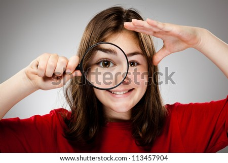 Girl holding magnifying glass on gray background
