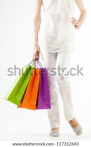 Girl holding multicolored shopping paper bags - closeup shot on white background - stock photo