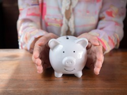 girl holding or protecting ,pointing at hole under white piggy bank in hands with smiling face,  saving money is key to susses in business and life concept