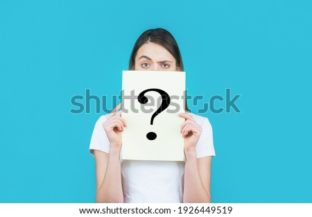 Girl holding paper question mark. Anonymous, woman question, incognita. Anonymous woman. Female incognita.Girl question, anonymous, incognita. Unknown woman holding question mark.