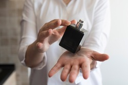 Girl holding perfume on the palm of her hand. Small black dicey bottle with silver cap. Wearing white shirt.