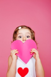Girl holding pink paper heart in hands