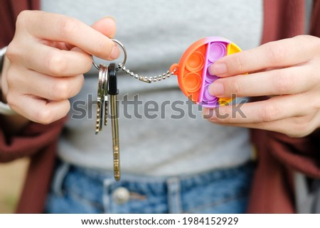 Girl holding rainbow bubble pop it fidget key chain. For autistic patients to relieve stress, help restore mood. Squeeze sensory game. Simple dimple. Push pop for homeschool or office, stress reliever Stock photo ©