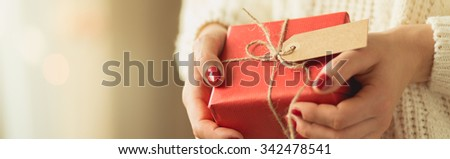 Girl holding red box of christmas present