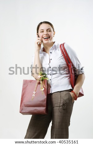 Girl holding shopping bag, talking on the phone and laughing out loud showing happy expression