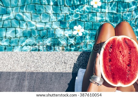 Girl holding watermelon in the blue pool, slim legs, instagram style. Tropical fruit diet. Summer holiday idyllic. #387610054
