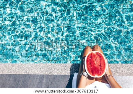 Girl holding watermelon in the blue pool, slim legs, instagram style. Tropical fruit diet. Summer holiday idyllic. #387610117