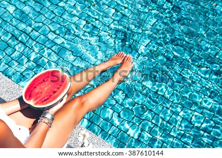 Girl holding watermelon in the blue pool, slim legs, instagram style. Tropical fruit diet. Summer holiday idyllic. #387610144