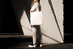 Girl holding white tote bag, template can be used for your design