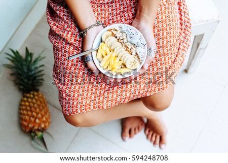 Girl holdingin hands smoothie bowl with mixed tropical fresh fruits, top view from above. Summer healthy diet, vegan breakfast.