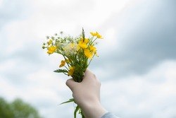 girl holds a bouquet of wild flowers against the sky
