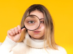 Girl holds a magnifying glass in front of her eye and looks at camera. Observant young woman with magnifying glass. Exploring what's around us. Detailed review of interesting object.