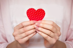 Girl holds a red heart in her hands, close up. Female hands holding a heart in her hands, Valentine's Day, love, romance background