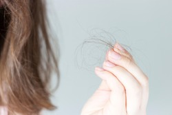 Girl holds a strand of hair front view, hair loss concept