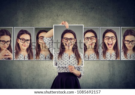 Girl holds and changing her face portraits with different expressions. Woman expressing different emotions #1085692157