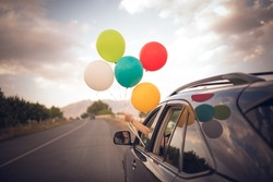 Girl holds colorful balloons out from the window of the car. Freedom, happiness, road trip and celebration concept.
