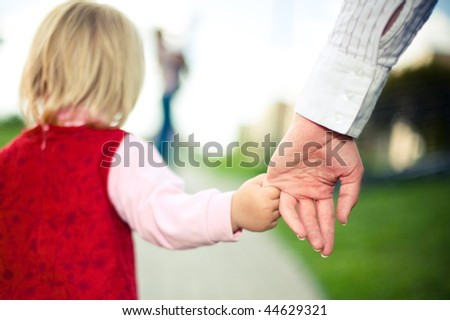girl holds her mother by hand