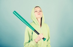 Girl hooded jacket hold baseball bat blue background. Woman in baseball sport. Baseball female player concept. She is dangerous. Girl troublemaker. Woman play baseball game or going to beat someone.