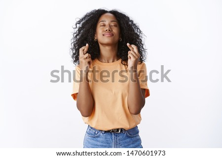 Girl hopes god hears prayers making wish desire come true. Hopeful attractive young female student wishes pass university exams close eyes raise head sky, cross fingers good luck white background #1470601973