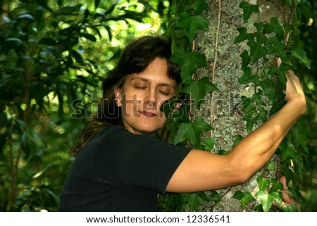 girl hugging a tree in a background of green vegetation